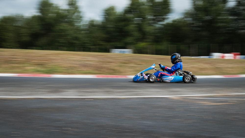 man riding blue and black go kart on track during daytime