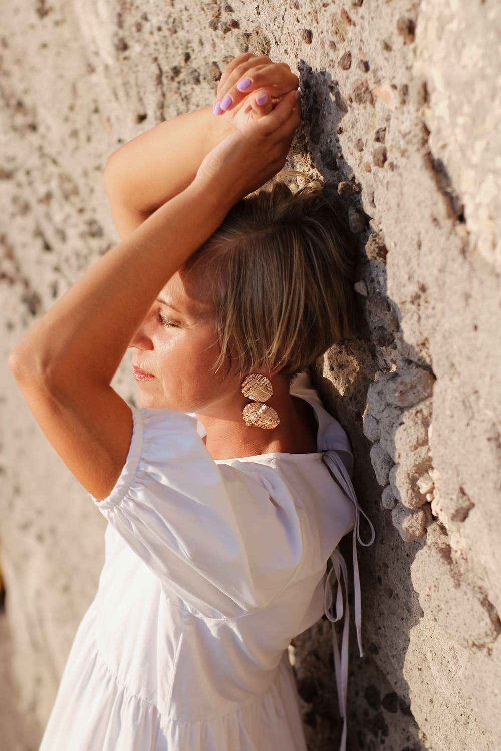woman in white sleeveless dress leaning on brown rock during daytime