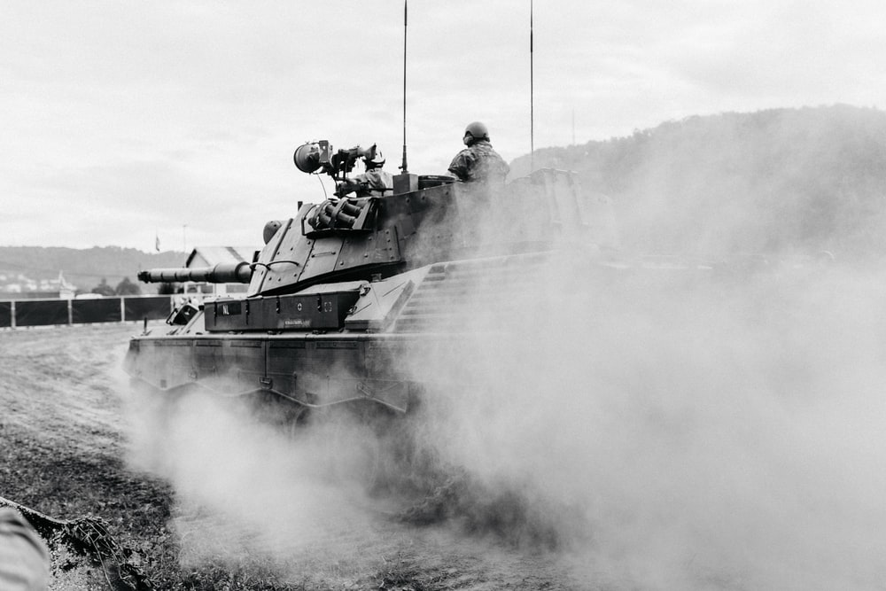 grayscale photo of soldiers on battle tank