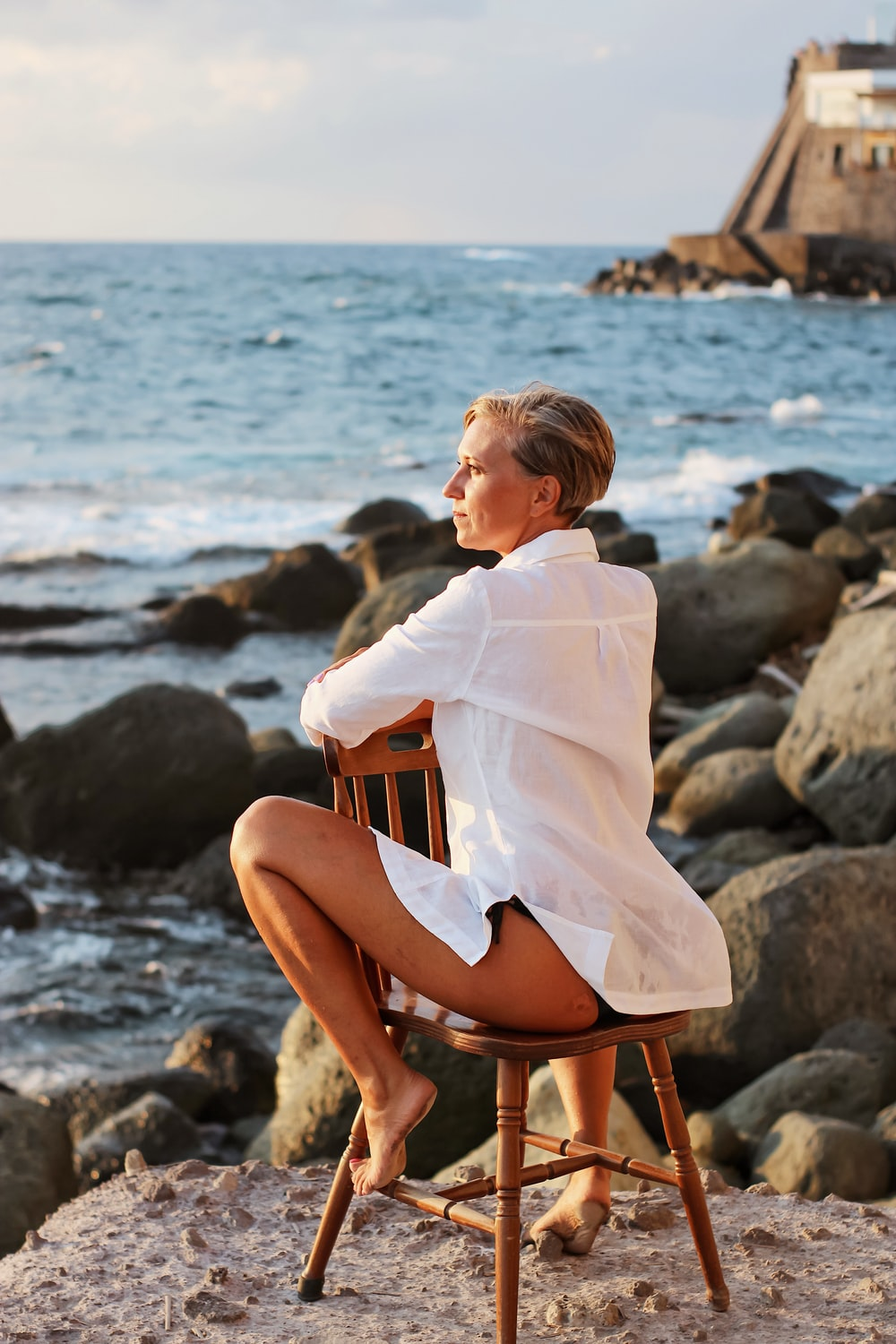 woman in white long sleeve shirt sitting on brown wooden chair on beach during daytime