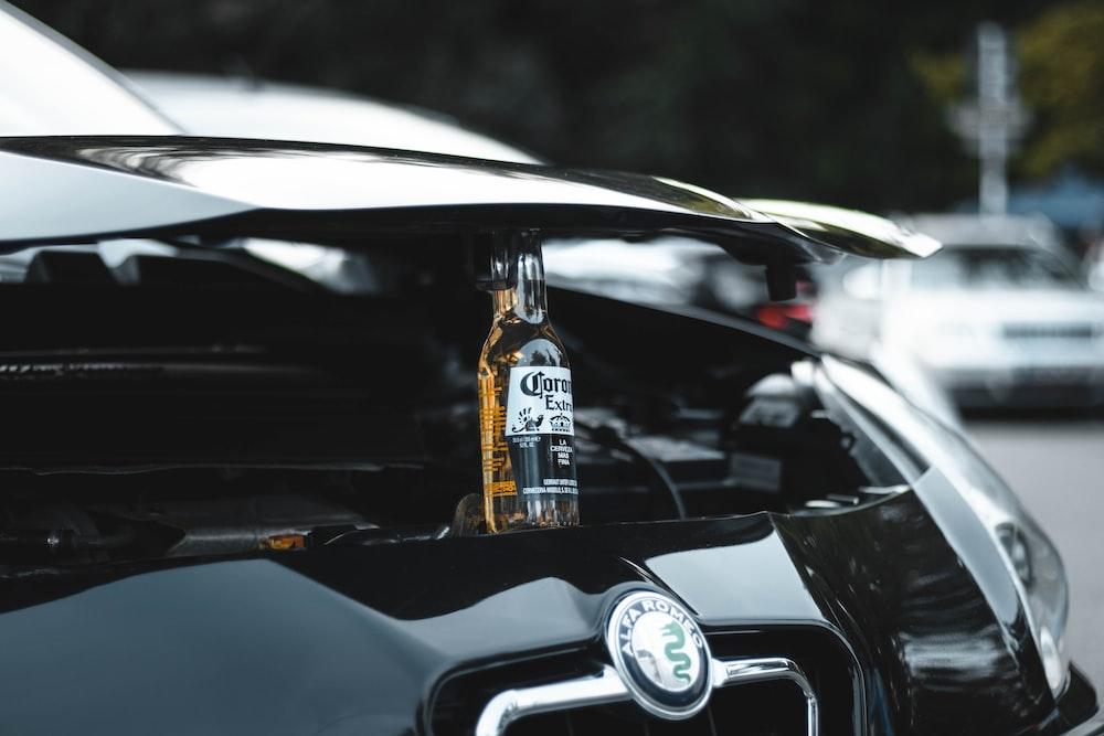 clear glass bottle on black car