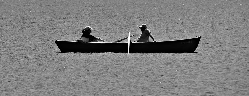 2 men riding on boat in grayscale photography