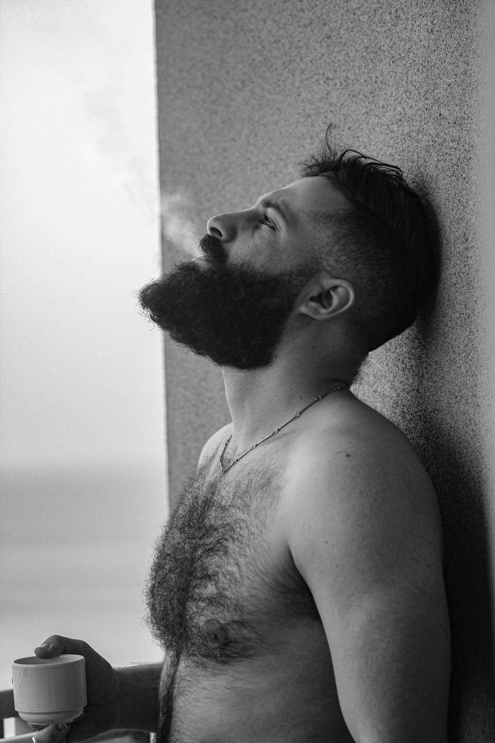 topless man leaning on wall