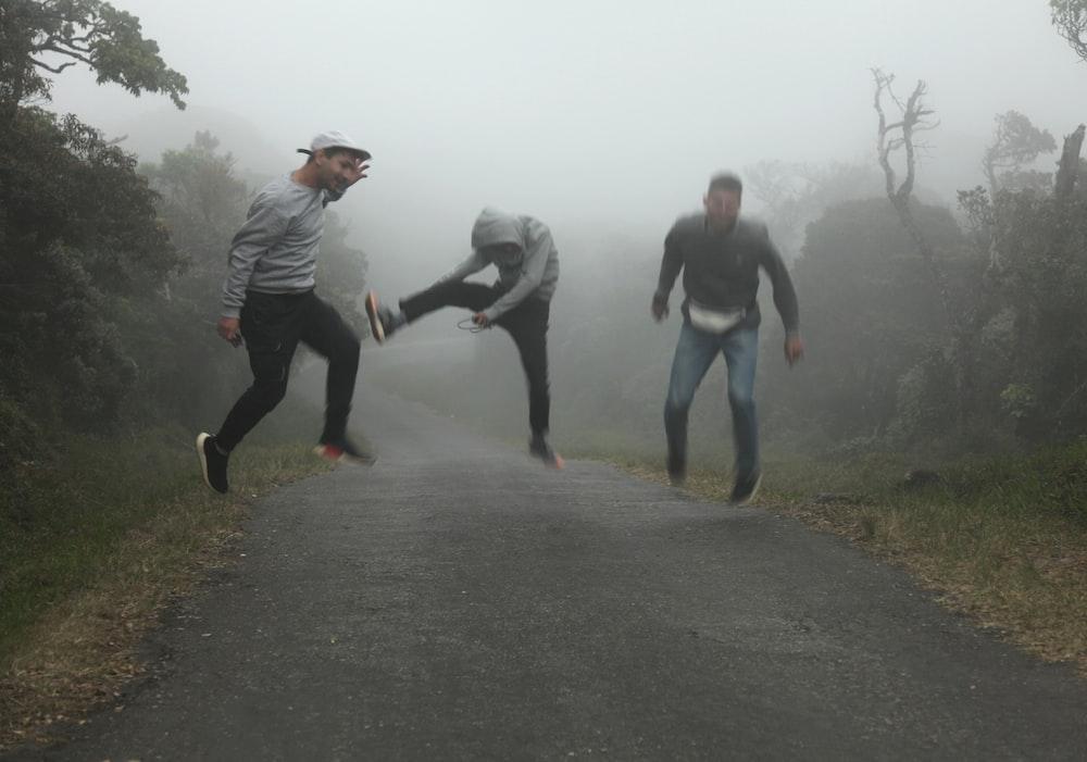 3 men running on road during daytime