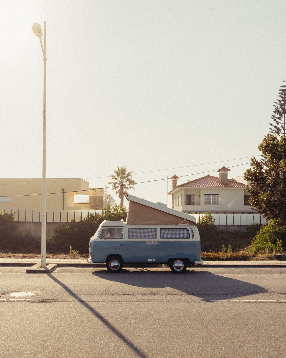 blue van parked on gray concrete road during daytime