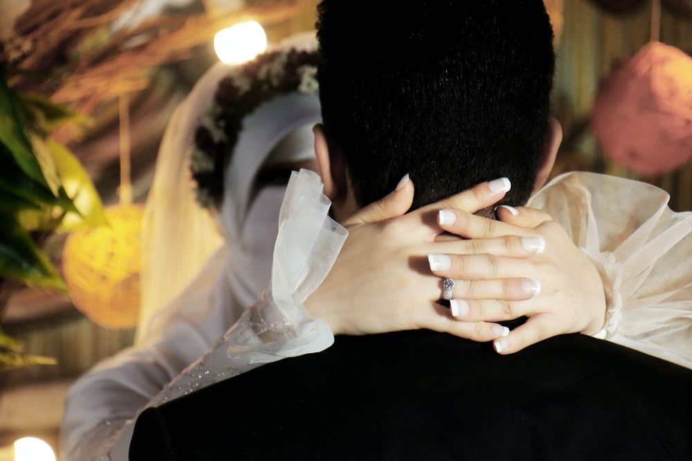 man in black shirt covering face with white textile