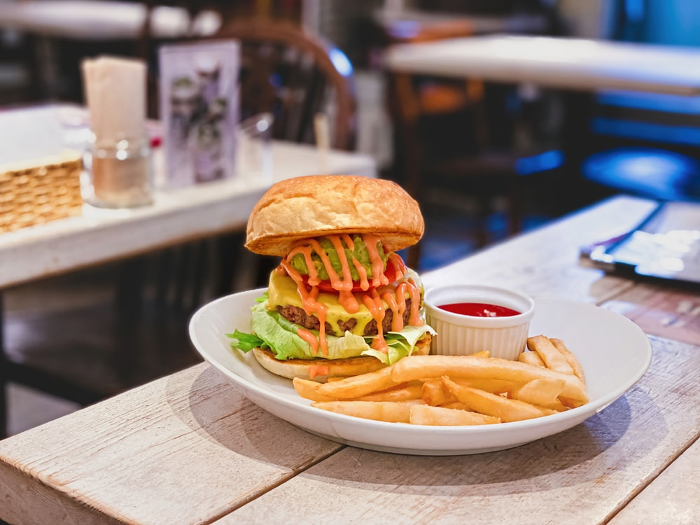 burger with lettuce and fries on white ceramic plate