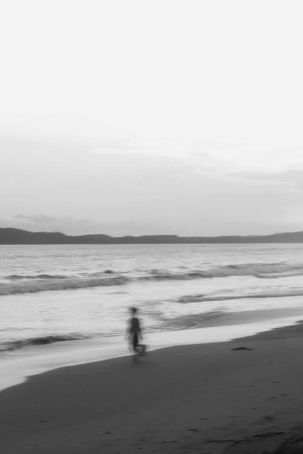 silhouette of 2 people walking on beach during daytime