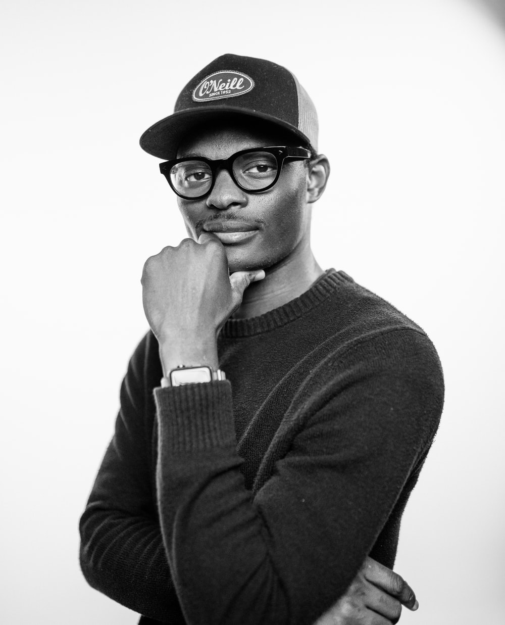 man in black sweater wearing black cap