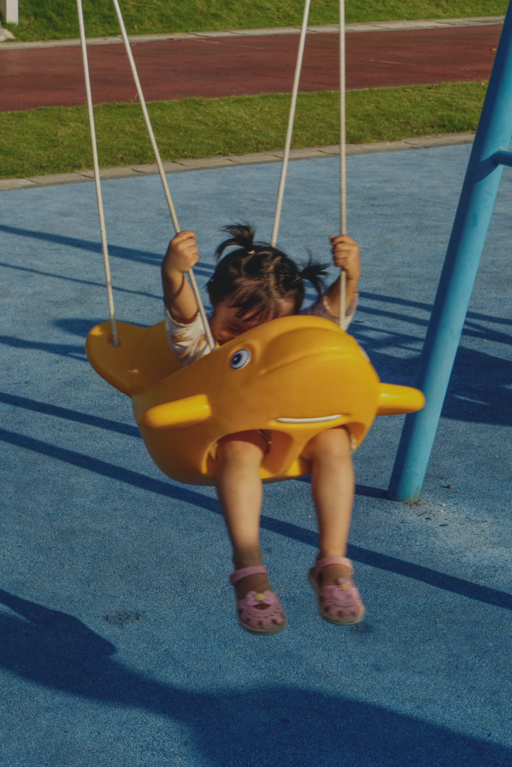 girl in yellow shirt sitting on yellow swing