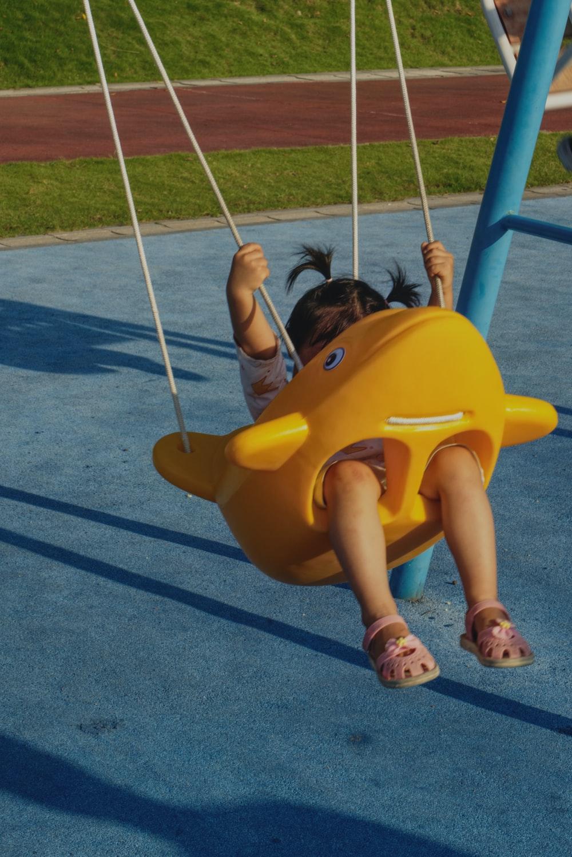girl in yellow shirt riding yellow swing
