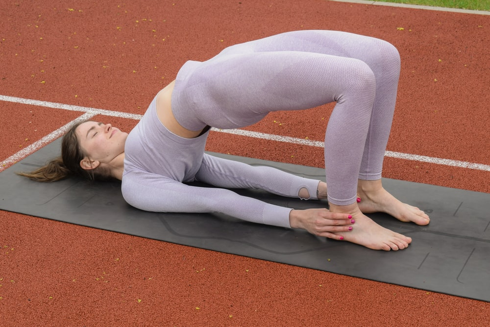 woman in white tank top and gray leggings lying on gray yoga mat