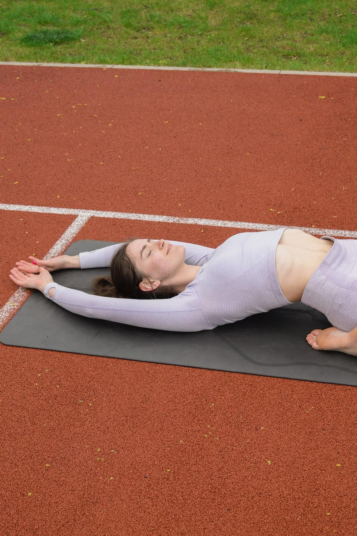 woman in white long sleeve shirt lying on gray mat