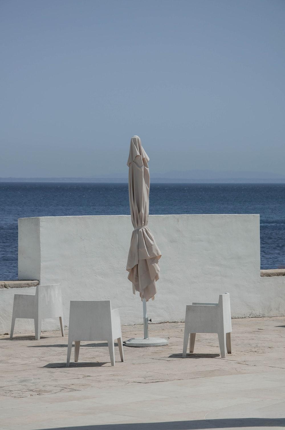 white and brown umbrella on white concrete table near blue sea during daytime