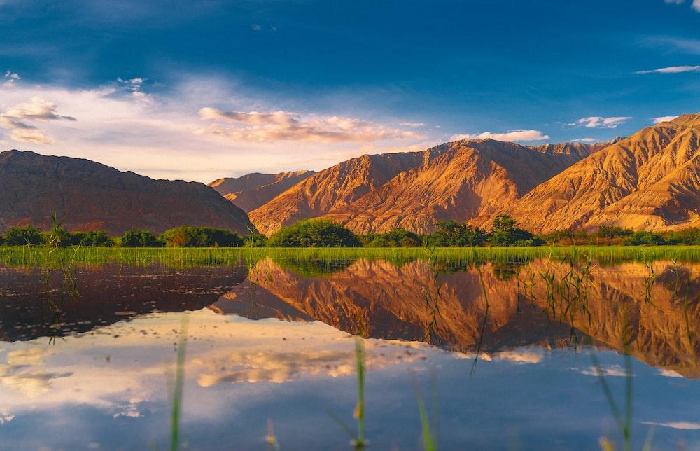 brown mountain beside lake under blue sky during daytime