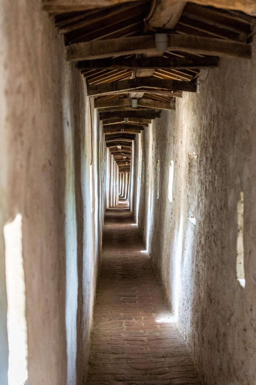 brown wooden pathway in between concrete walls