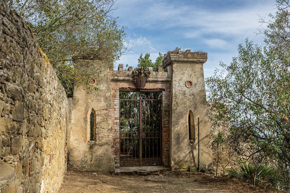 brown brick building with black metal gate