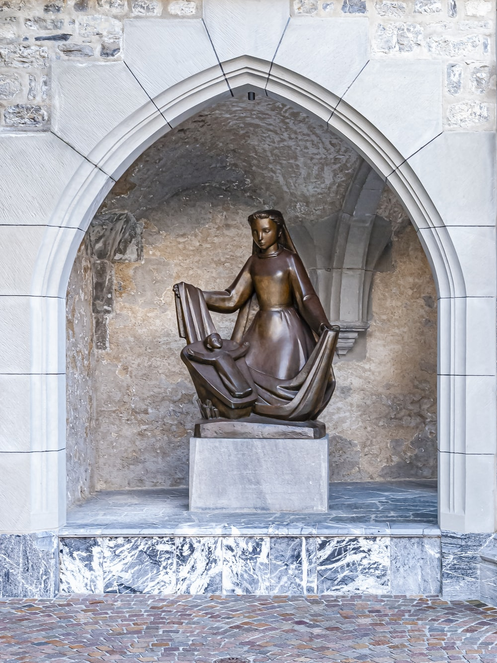 brown statue on gray concrete wall