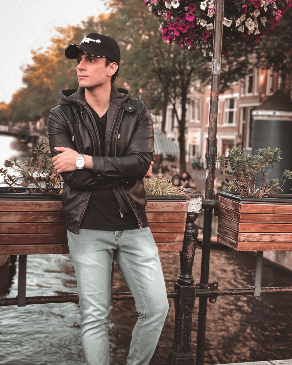 man in black leather jacket and gray pants standing near brown wooden bench during daytime