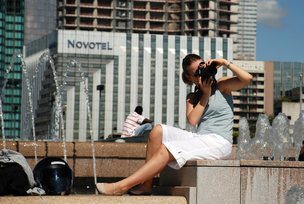 woman in white dress shirt and white shorts sitting on concrete bench