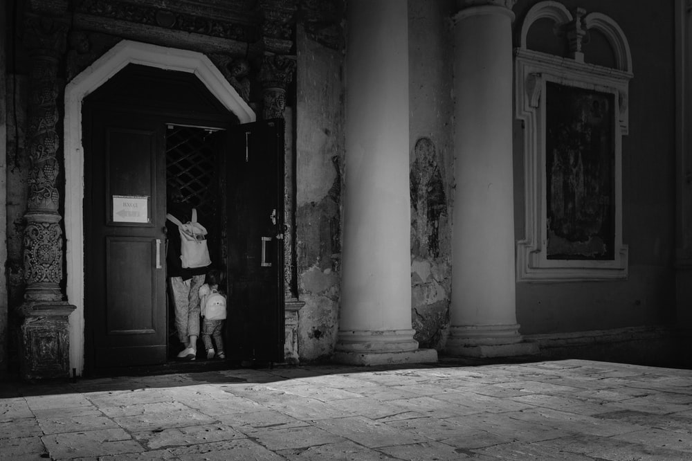 grayscale photo of man in black jacket standing near door