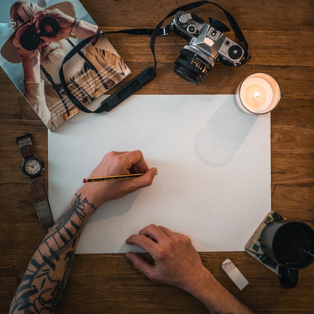 person holding white printer paper near black dslr camera and white ceramic mug