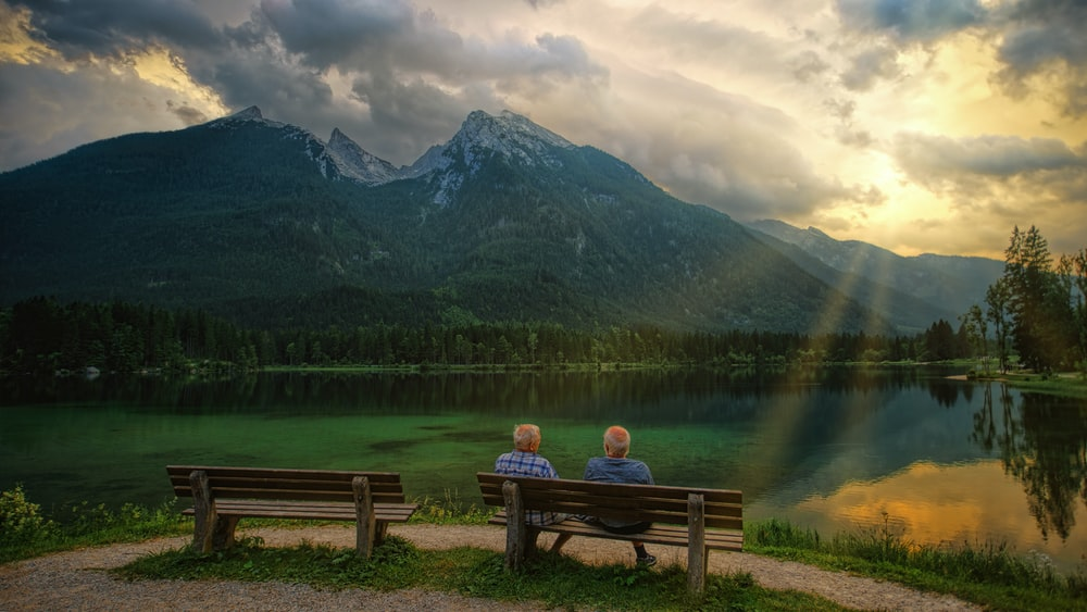 person sitting on brown wooden bench facing lake and mountains during daytime