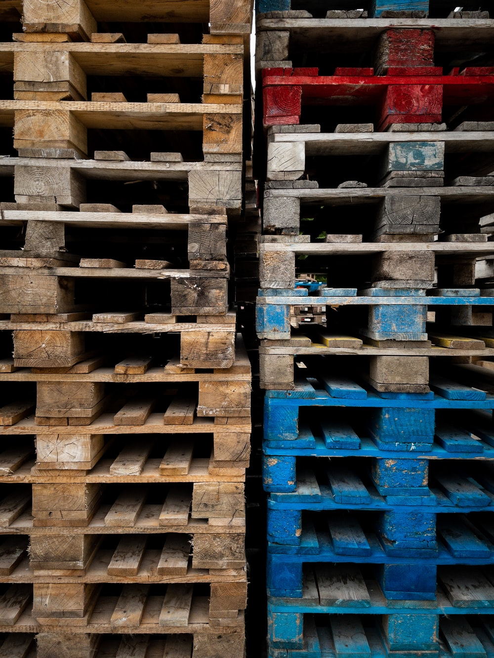 brown wooden crates with red and blue plastic crates