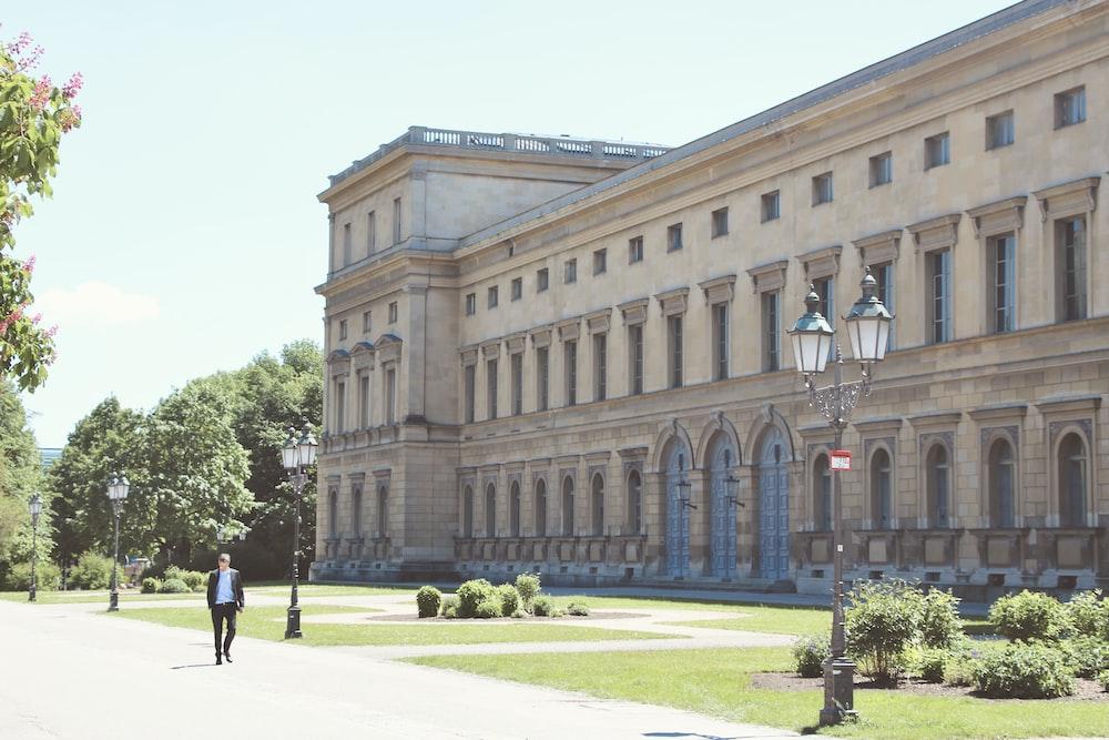 people walking on pathway near brown concrete building during daytime