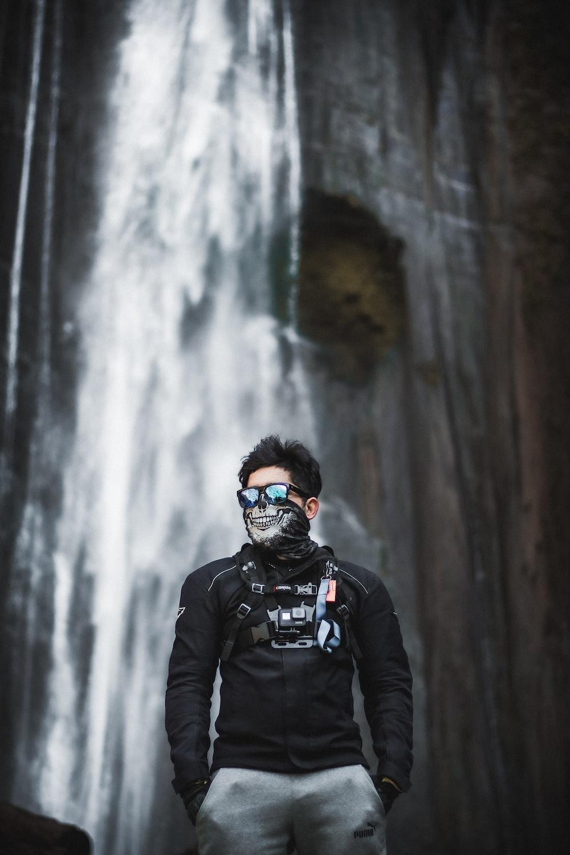 man in black jacket wearing black goggles standing near waterfalls during daytime