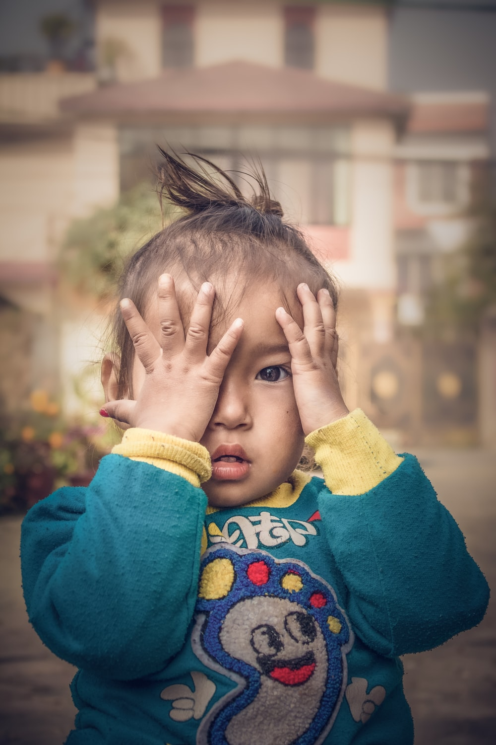 child in blue sweater covering face with yellow textile
