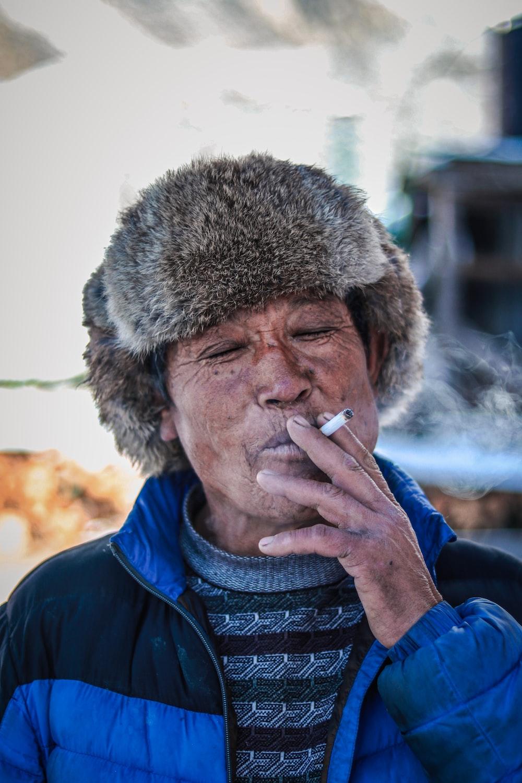 man in blue jacket smoking