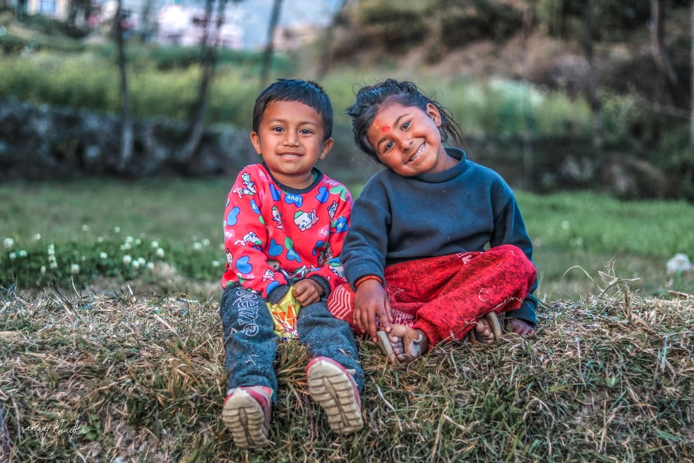 2 boys sitting on grass field during daytime