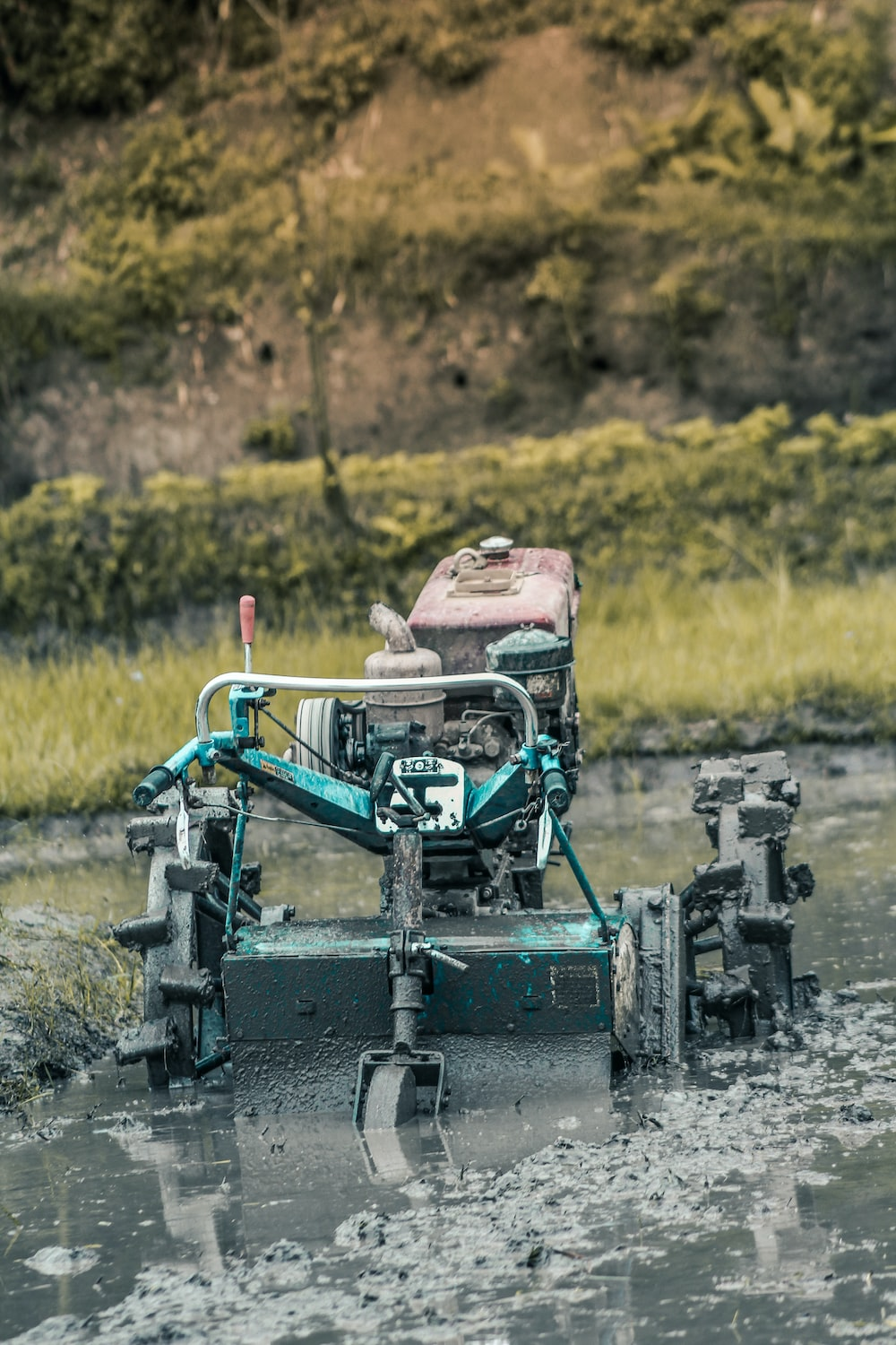 green and black metal machine on green grass field during daytime