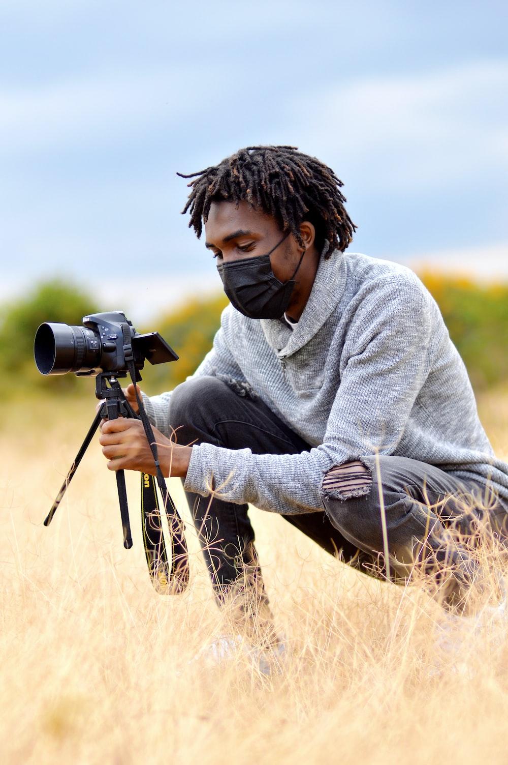 man in gray sweater using black dslr camera