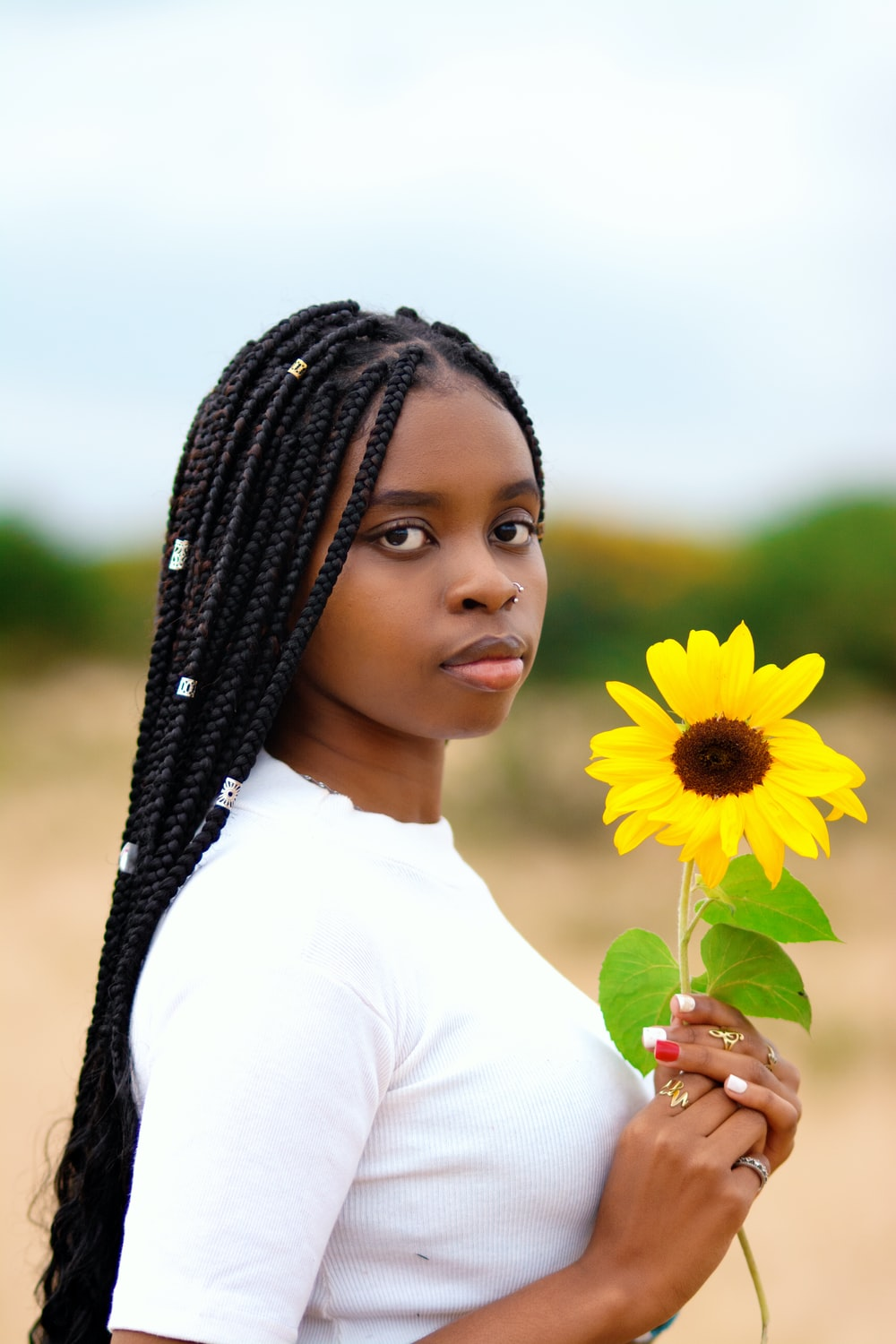 woman in white shirt holding yellow sunflower during daytime