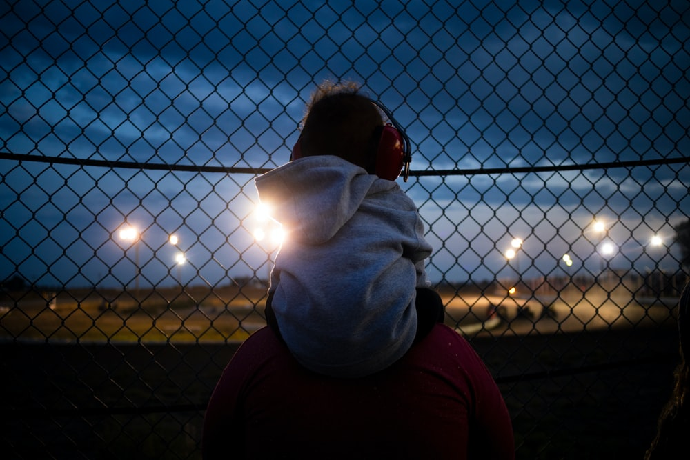 man in white hoodie standing near fence during sunset