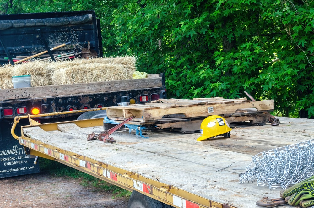 yellow and black heavy equipment on brown wooden pallet