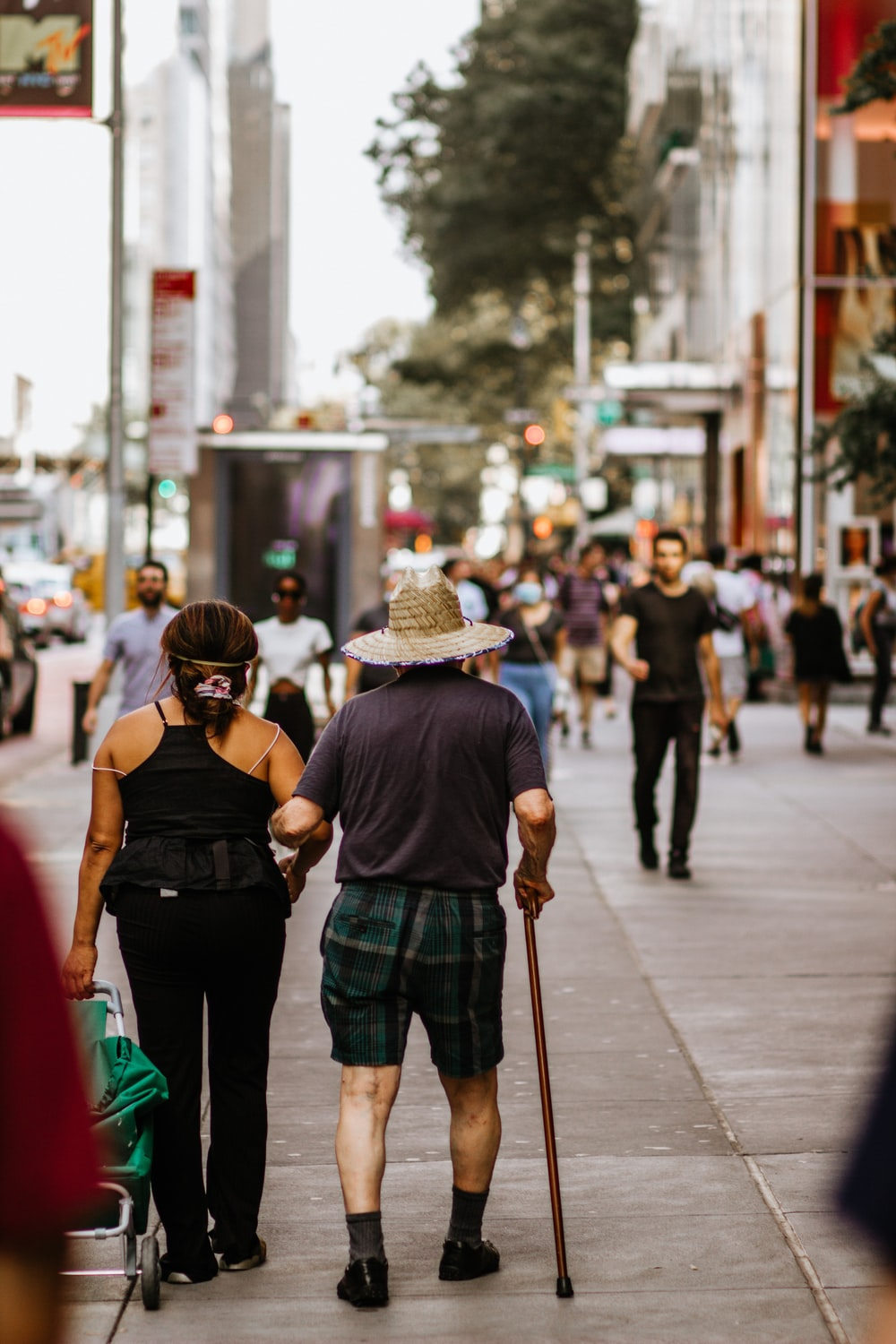 woman in black tank top and green pants walking on street during daytime