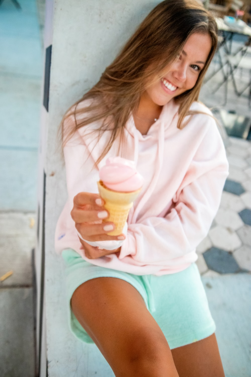 woman in pink long sleeve shirt holding clear glass cup