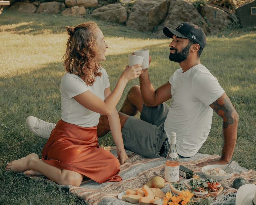 man and woman sitting on ground with food on ground during daytime