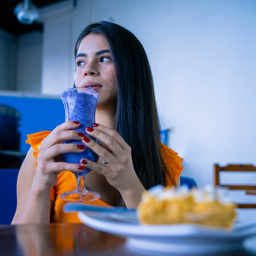 woman in yellow shirt drinking from clear drinking glass