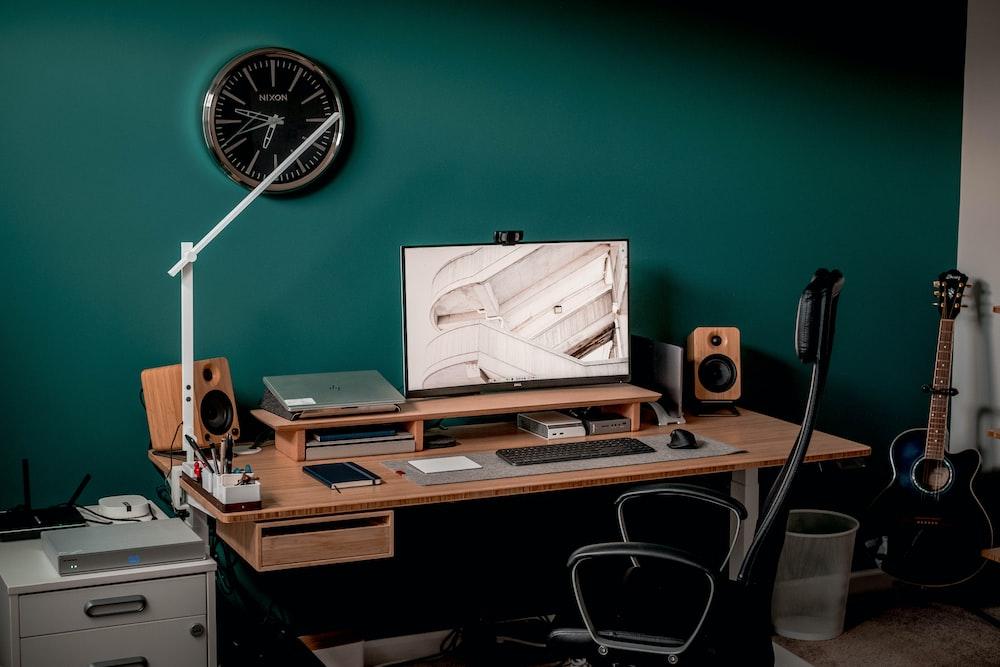 black and silver speaker on brown wooden desk