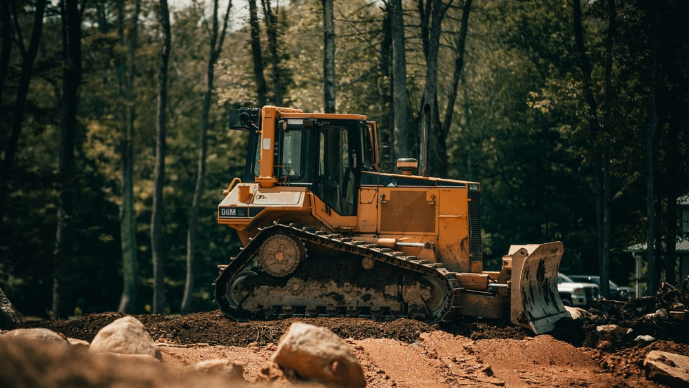 yellow and black front loader on forest during daytime