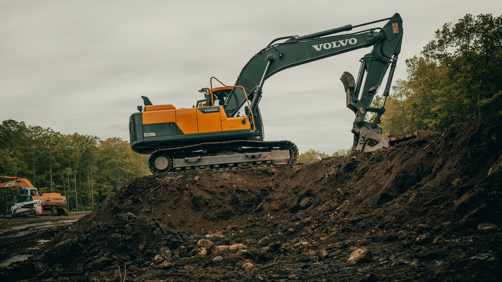 orange and white excavator on brown ground during daytime