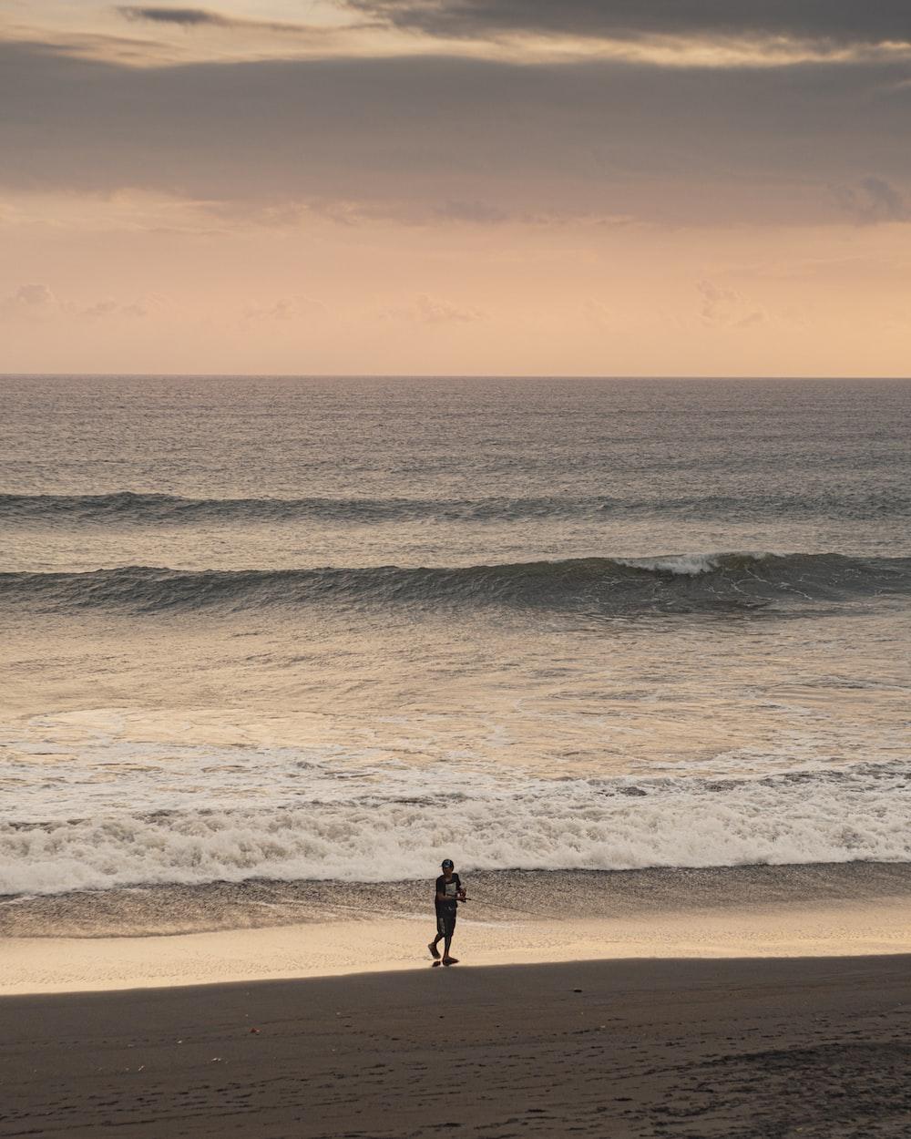 man in black shirt walking on beach during sunset