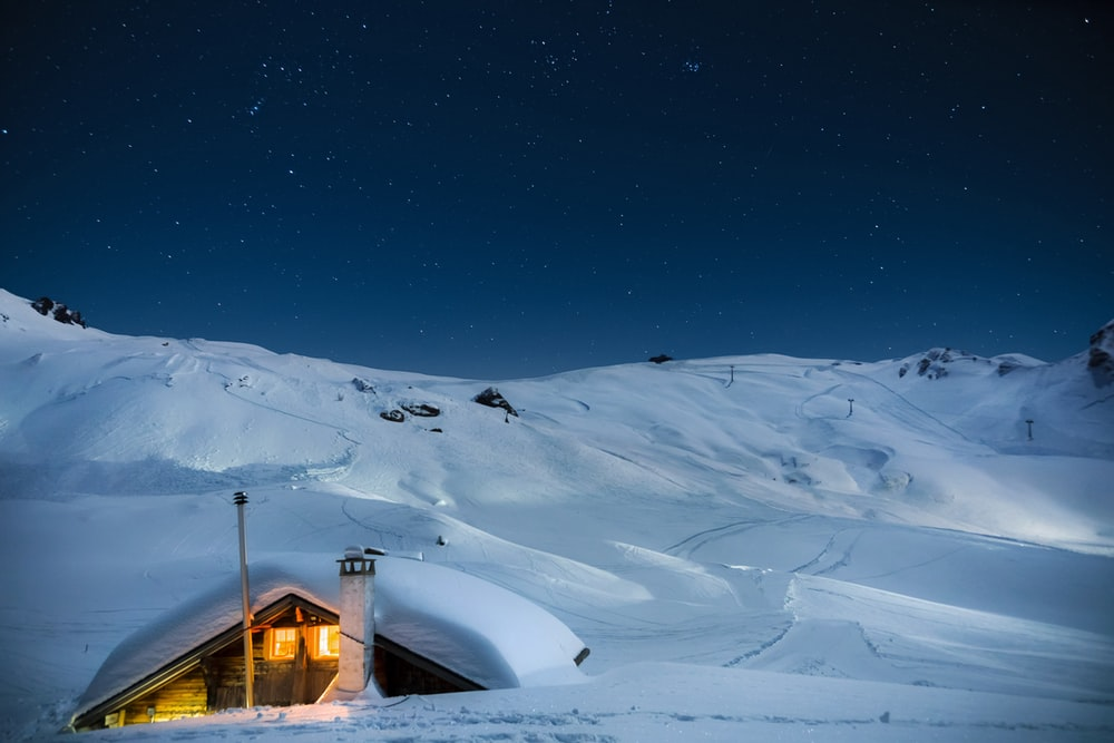 brown wooden house on snow covered mountain during night time
