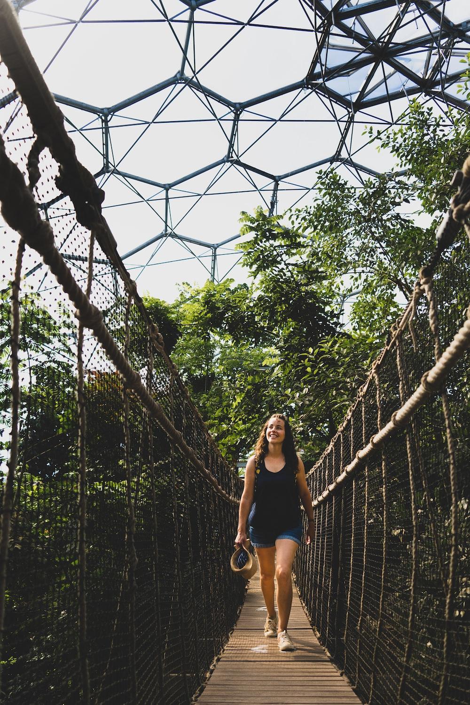 woman in black tank top and black shorts standing on hanging bridge during daytime