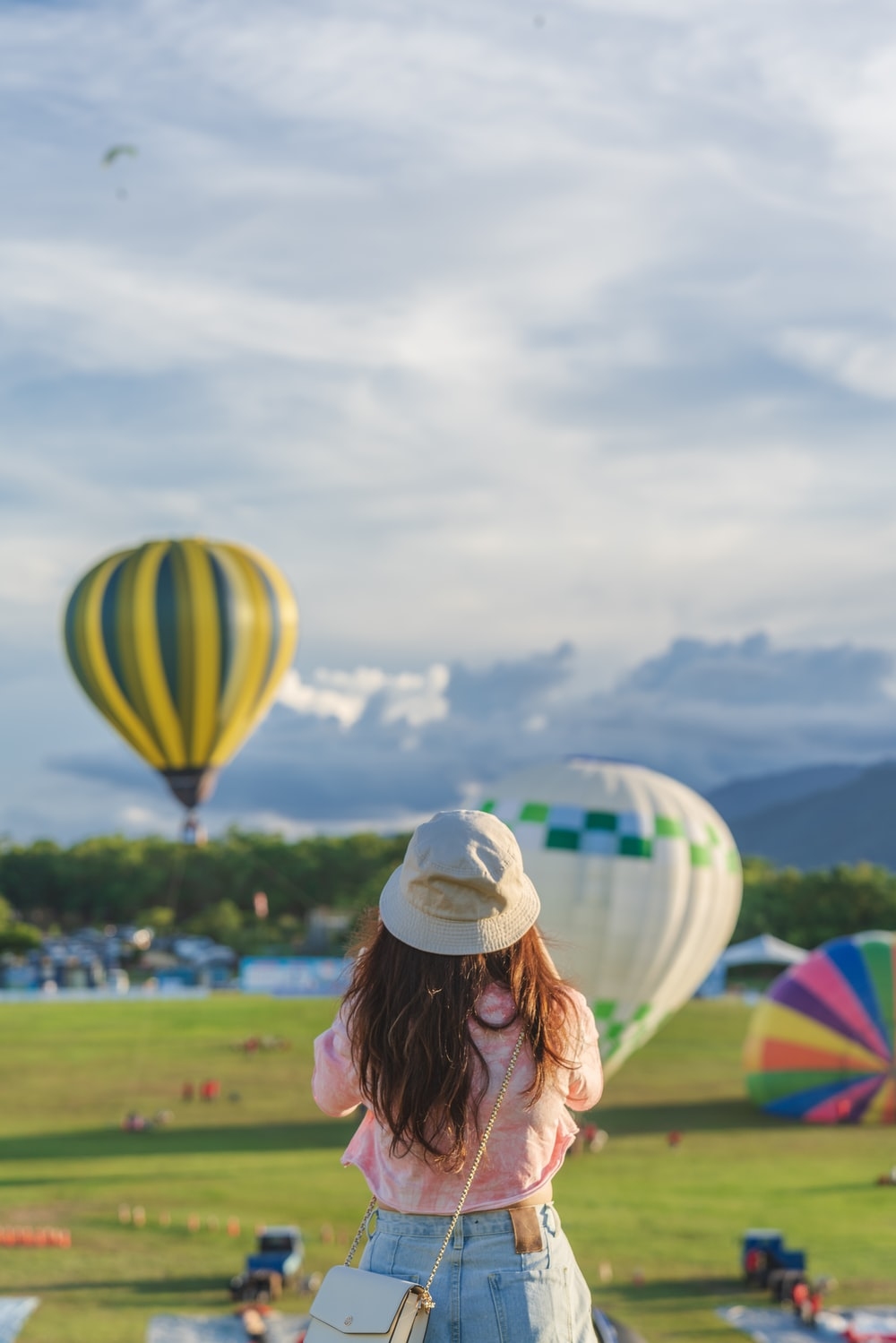 woman in white sun hat holding yellow green and blue hot air balloon