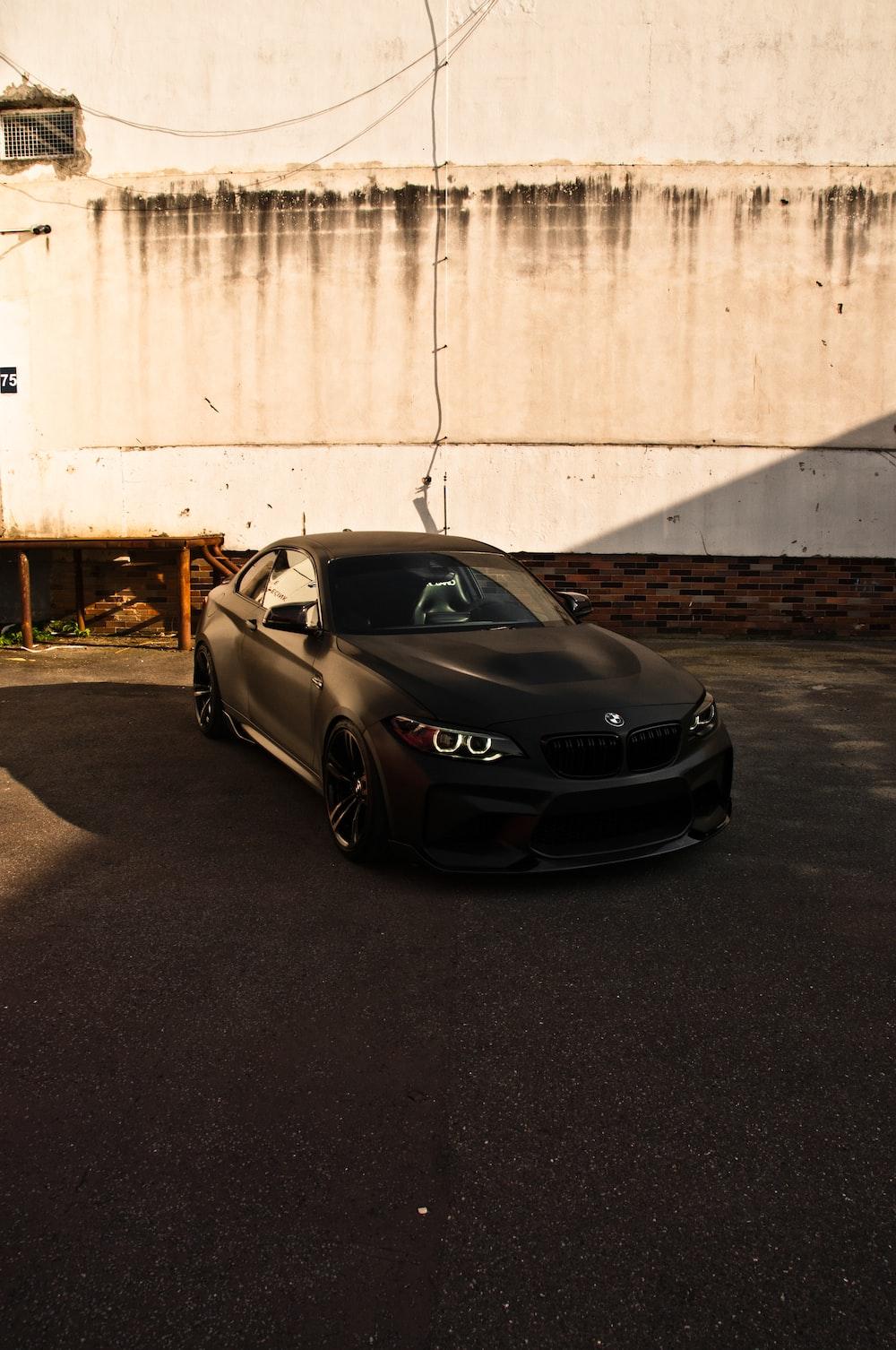 black porsche 911 parked beside white wall